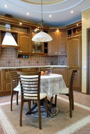 cozy kitchen: walnut cupboards, round table covered with beautiful white crocheted table-cloth with rubicund apples on it, four chairs, low pulled down lamp; pertfect illumination