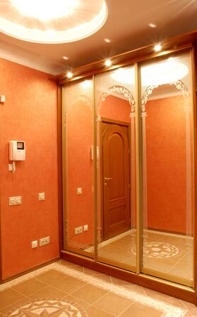 hall designed in orange colour, wadrobe with a mirror, perfect illumination, lamp on the ceiling is placed in a big rosette Stock Photo