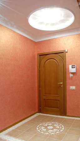 hall designed in light orange colour, lamp is placed in a big rosette