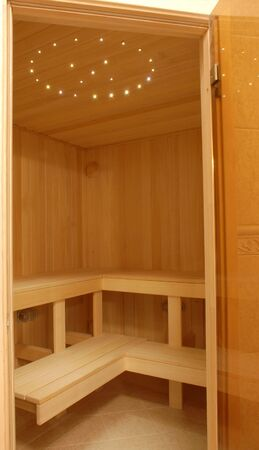 little cozy modern sauna of light wood nicely illuminated Stock Photo