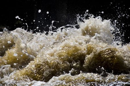 seething: foaming and splashing yellow waves of a river