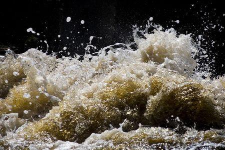 espumante: la formaci�n de espuma y salpicaduras de color amarillo olas de un r�o Foto de archivo