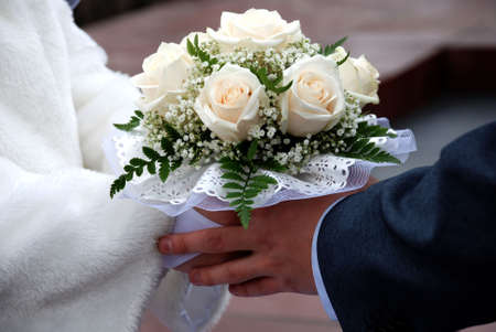 beatiful: joined hands of the newly-weds holding the wedding bouquet composed of beatiful white roses