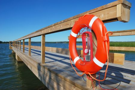 wooden berth with an orange ring-buoy on the seashore