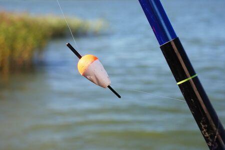 fishingline: fishing float of the rod against the seashore