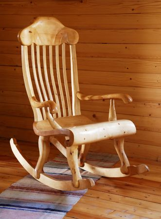 carved wooden rocking-chair in the country-style interior                               Stock Photo