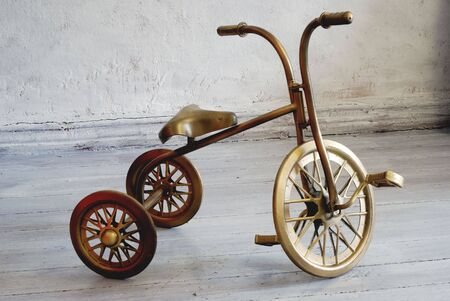 small childs golden three-wheeled bicycle on the white floor Stock Photo