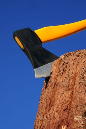 heavy ax put in stump against blue sky