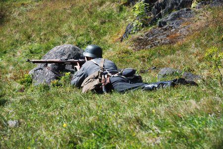 under fire: soldado con el fusil al amparo de fuego