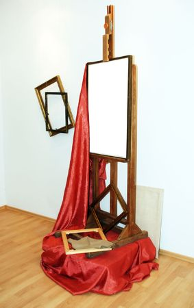 easel, red drapery and frames in studio of painter