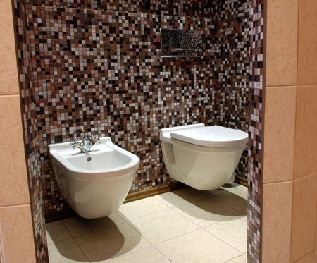 WC: lavatory pan and a bidet, stylish brown tiled mosaic walls Stock Photo