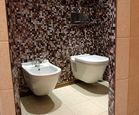 bidet: WC: lavatory pan and a bidet, stylish brown tiled mosaic walls Stock Photo