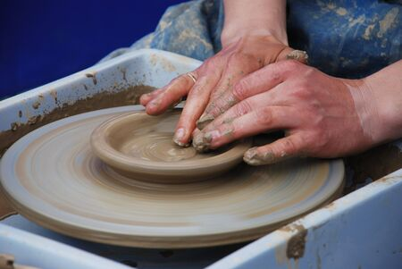 potters wheel: potters wheel and hands of craftsman hold a jug