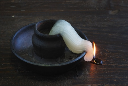 deformed candle-end in an old ceramic candlestick Stock Photo