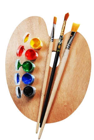 descriptive colour: artists wooden  palette with multiple colors and brushes Stock Photo