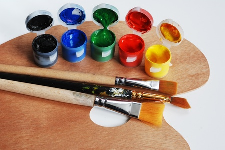 daubed: artists wooden  palette with multiple colors and brushes Stock Photo