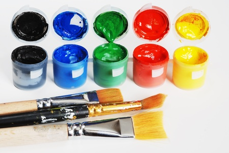 daubed: plastic containers with paint, black, blue, green, red, yellow and brushes over white