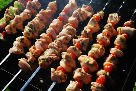 grilled meat on metal skewers cooking on a coal