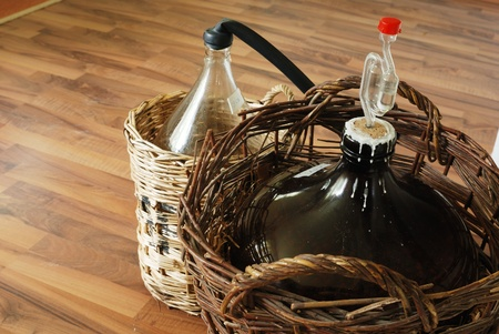 bottles of homemade wine in wicker baskets