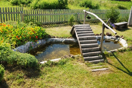 small garden pond with wooden bridge in summer Stock Photo