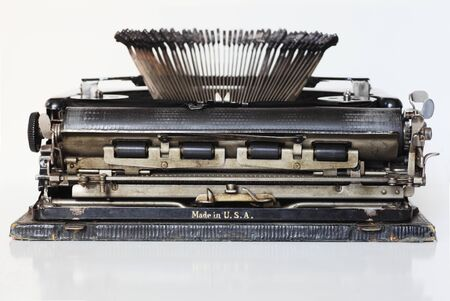 ancient portable typewriter over white background, back view photo