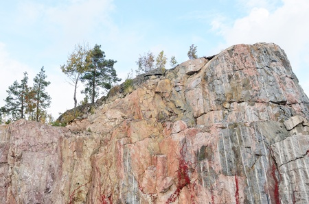 bedrock: trees on a vertical rock against blue sky Stock Photo
