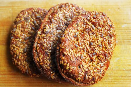 three sandwich buns with sesame seeds on wooden cutting board  photo