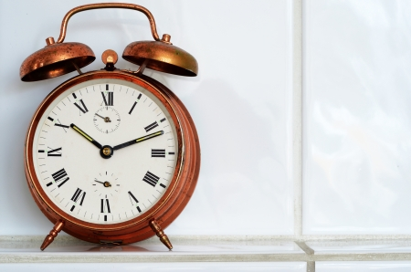 old-fashioned copper alarm clock on the mantelshelf  photo