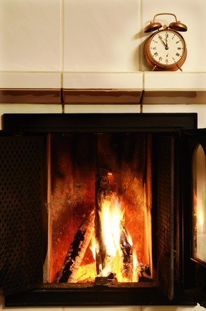 fireplace, flame and  old-fashioned copper alarm clock on the mantelshelf Stock Photo - 16899712
