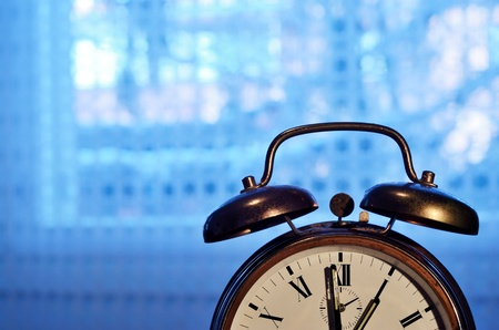old-fashioned copper alarm clock  against blue window Stock Photo