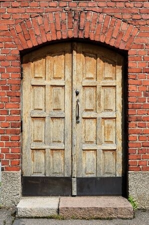 large yellow door in brick wall, vertical photo