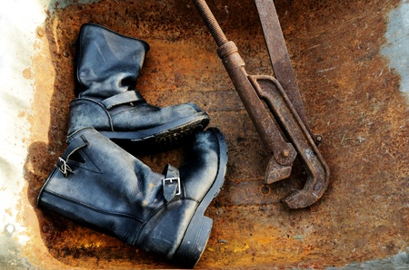 oldie: old vintage leather boots and rusty pipe wrench