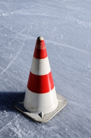 red white striped cones on the ice rink, vertical photo