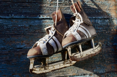 vintage pair of mens  ice skates hanging on a wooden wall photo
