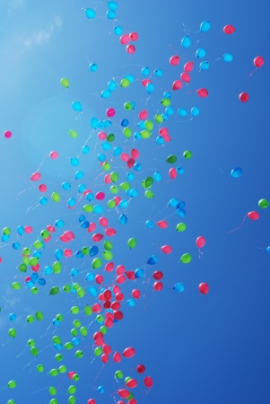 releasing: red, green and blue balloons flying in clear sky Stock Photo