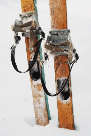 old wooden skis in the snow, vertical