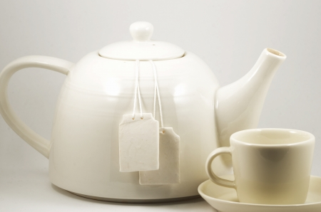 white ceramic teacup and teapot with two blank labels photo