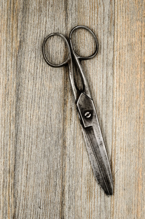 pair of old scissors on a wooden background photo