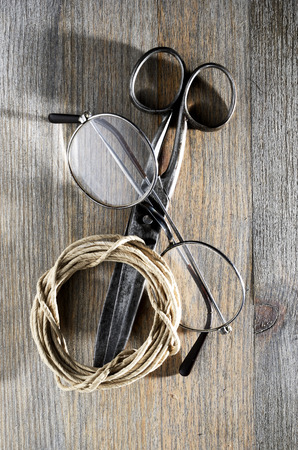 old scissors, glasses and hank of packthread over wooden background Stock Photo - 26244571