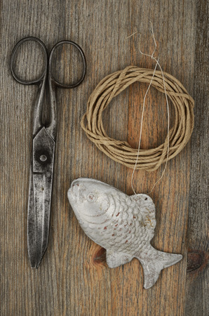 fingerling: old scissors, glasses, fish and hank of packthread over wooden background