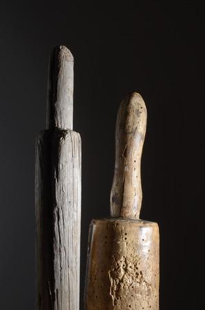 phallus: two wooden phallic object on a dark background Stock Photo