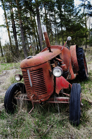 old rusty tractor in the forest, Finland photo