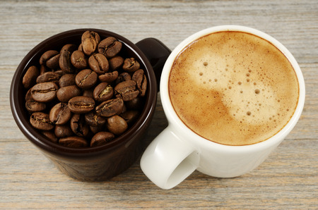 two cups of coffee and beans on wood photo