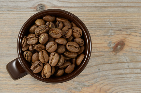 brown cup with coffee beans on wooden background photo