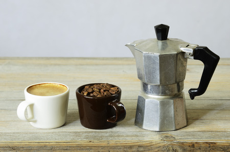 two cups of coffee and beans and percolator on wood photo