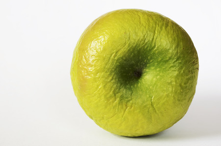 contracted: contracted green dry apple against white background Stock Photo