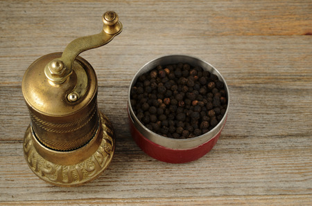 major household appliance: old oriental pepper mill and black pepper peas on wooden background Stock Photo
