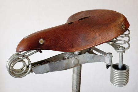 metal spring: old-fashioned vintage leather bike saddle with metal spring