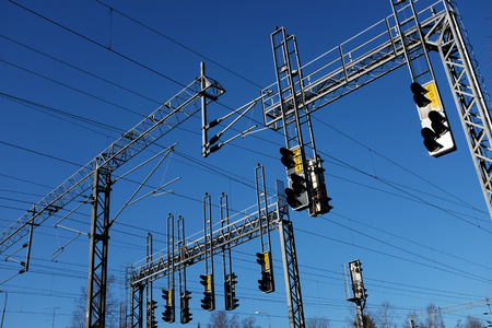 railway points: train station and lines with electricity pylon against blue sky
