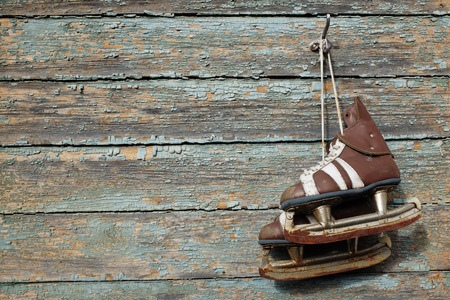 figure skates: vintage pair of mens  ice skates hanging on a cracked paint wall